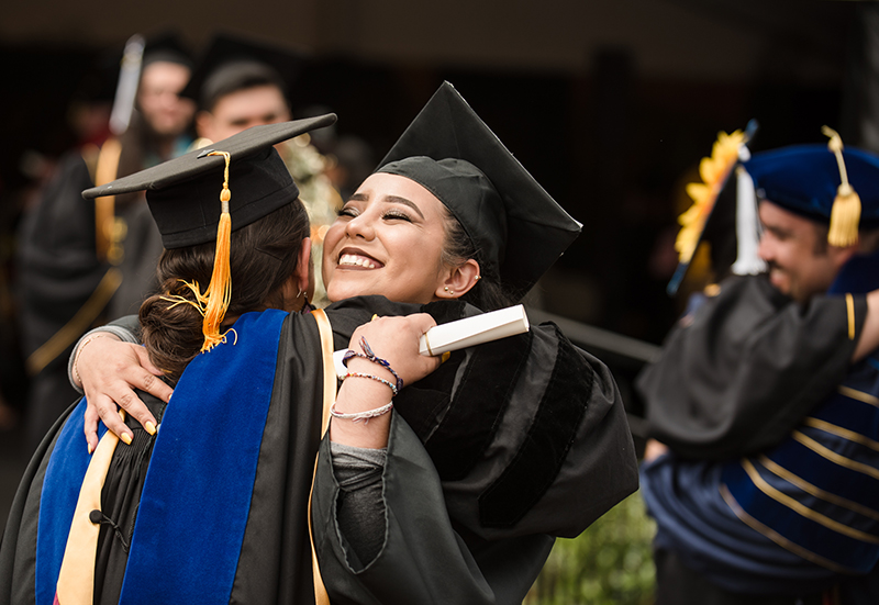 A female student hugging a faculty member at Commencement