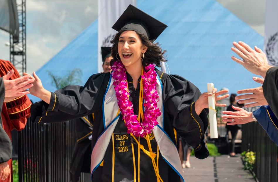 Graduating students walking down from stage with arm spread out